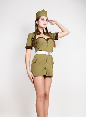 sexy fashionable woman in military uniform and forage-cap, put a hand to her head, salutes
