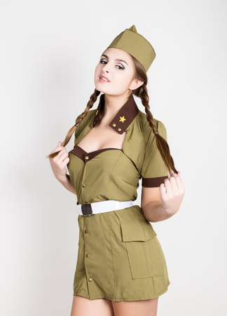sexy fashionable woman in military uniform and forage-cap, posing
