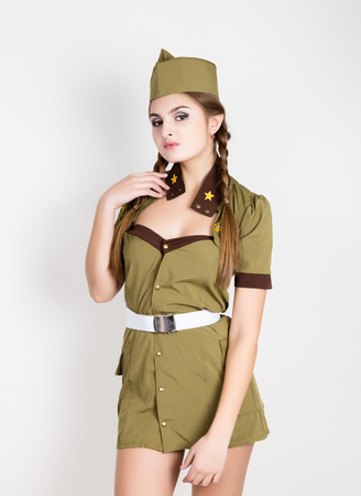 provocative woman: sexy fashionable woman in military uniform and forage-cap, posing