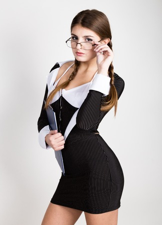 affable: sexy secretary, portrait of beautiful brunette business lady with glasses and wearing in pinstripe suit