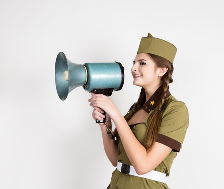 army face: sexy fashionable woman in military uniform and garrison cap, holding bullhorn and screaming