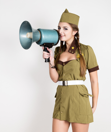 garrison: sexy fashionable woman in military uniform and garrison cap, holding bullhorn and screaming