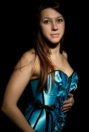 portrait of sexy young woman in corset with lacing posing on a dark background