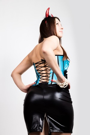 Young beautiful girl in blue corset with red horns looks like pretty Devil Stock Photo