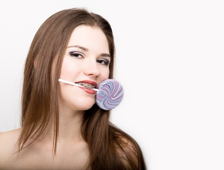 Portrait of teen girl showing dental braces and holding candy Stock Photo
