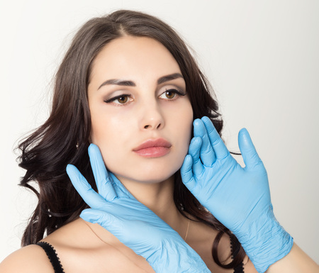 Closeup of Beautiful young woman gets injection in eye and lips area from beautician. cosmetology concept Stock Photo