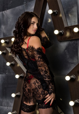 fashion sexy young woman in lacy lingerie and stockings posing on steel background with big star Stock Photo