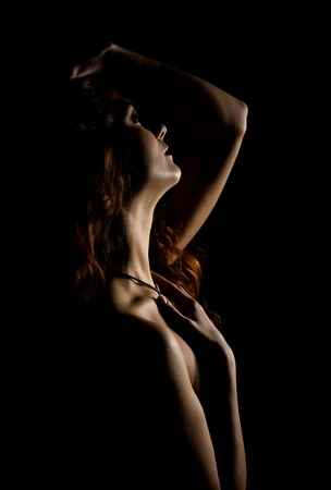 Elegant curves of female shoulders and neck, Redhead girl on a dark background Standard-Bild