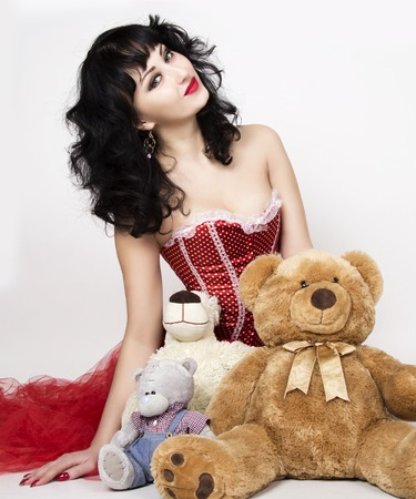 young and beautiful woman in red ccorset sitting on a floor with teddy bear