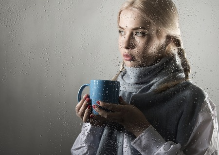 contrasty: young woman dressed in sweater drinking coffee or tea, posing behind transparent glass covered by water drops