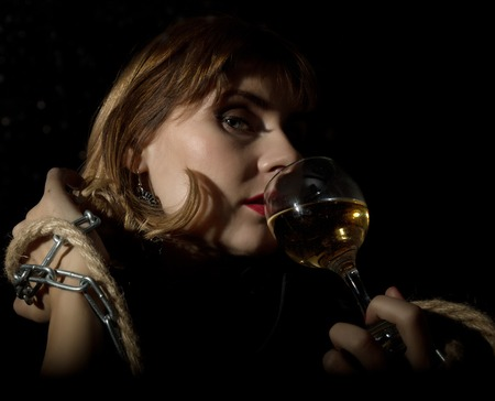mysterious young woman with a glass of wine posing behind transparent glass covered by water drops. on a dark background