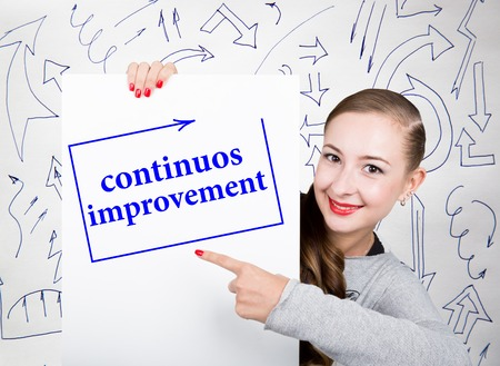 writing on screen: Young woman holding whiteboard with writing word: continuos impruvement. Technology, internet, business and marketing. Stock Photo