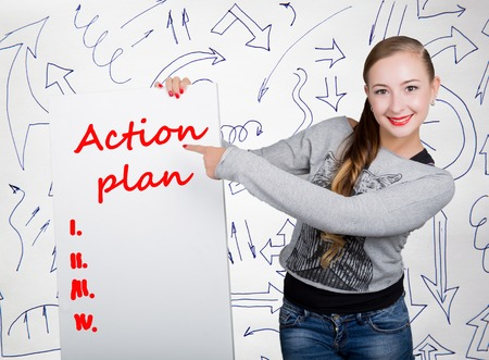 agile: Young woman holding whiteboard with writing word: action plan. Technology, internet, business and marketing. Stock Photo