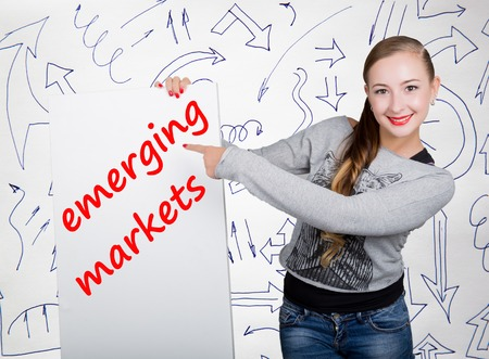 Young woman holding whiteboard with writing word: emerging markets. Technology, internet, business and marketing. Stock Photo