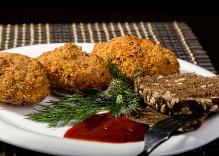 Homemade meat cutlets with parsley, ketchup and bread on white plate