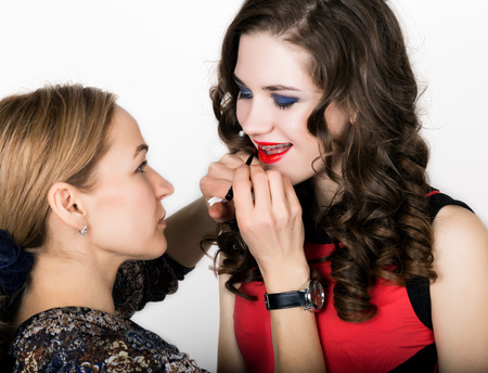 Makeup artist applies lipstick. Beautiful fashion woman face. Perfect makeup. Lipgloss brush. Stock Photo