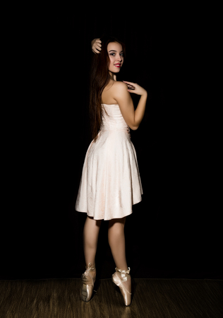 Young ballerina with a perfect body is dancing in pointe shoes on dark background