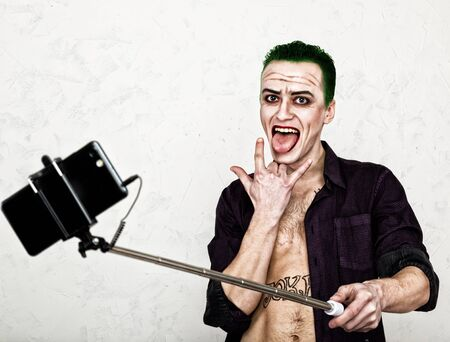 psychotic: guy with crazy joker face, green hair and idiotic smile. carnaval costume. making selfy photo