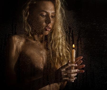 暗い背景にキャンドルと巻き毛のヌード金髪女性 写真素材