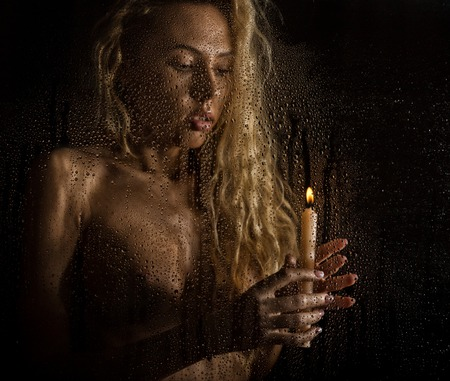 curly nude blonde woman with candle on dark background Stock Photo