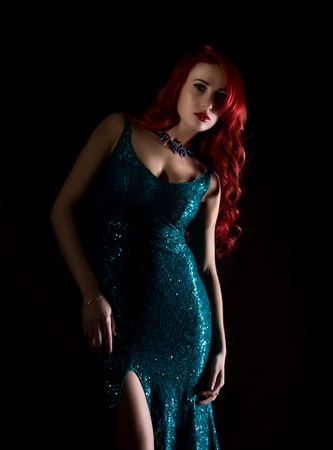 beautiful redhead woman with big tits in a tight dress posing on a dark background