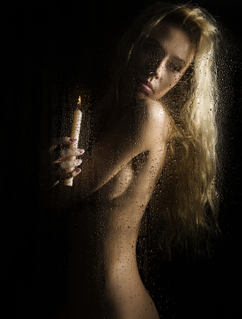 curly nude blonde woman with candle on dark background Stockfoto
