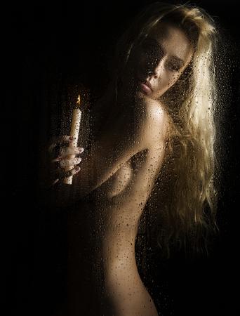 Krullend naakt blonde vrouw met kaars op donkere achtergrond