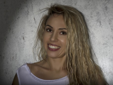 fashion portrait of blonde model posing near gray wall, girl in mans white shirts smiling