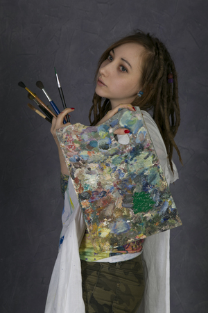 brash: Attractive young woman artist holds brush and palette, begins to draw a new paint