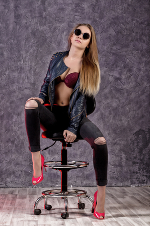 Beautiful urban trendy girl in black leather jacket and jeans posing on a high chair Stock Photo