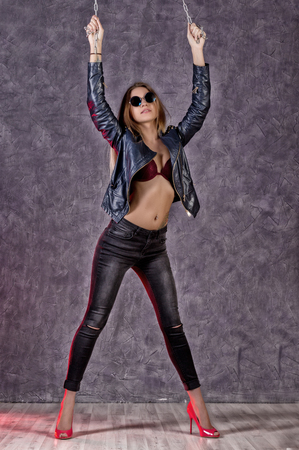 Beautiful urban trendy girl in black leather jacket and jeans holding on to chains Stock Photo