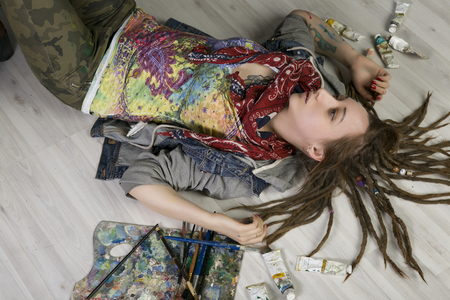 Attractive young female artist with dreadlocks lies on the floor, holds brushes, there are tubes with paints nearby