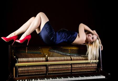 fashion young woman lies on old retro wooden piano with keyboard and posing