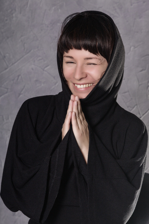 Praying woman in black dress with hood on a grey background