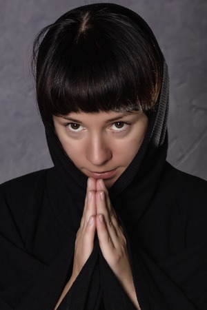 sins: Praying woman in black dress with hood on a grey background