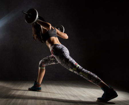 Sporty sexy girl with barbell on a dark background. Athlete doing exercises in the gym Foto de archivo