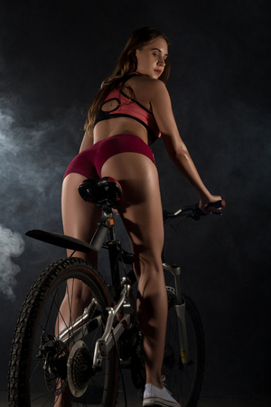 Young sporty woman with bicycle on a gray background with smoke Stock Photo