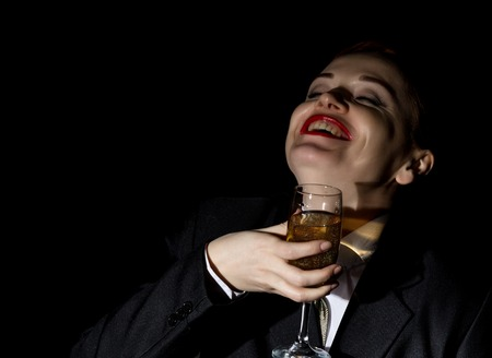 Strange girl in a mans suit drinks champagne, wildly and crazy laughs