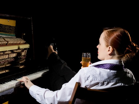 female musician dressed in a mans suit sitting next to the piano and drinks champagne