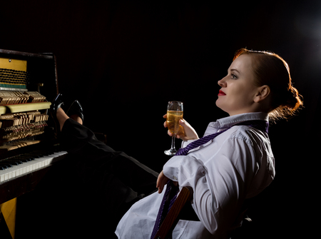 Elegant woman in a white shirt and tie sitting next to the piano and drinks champagne
