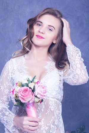 beautiful bride in a white peignoir with a bouquet of flowers