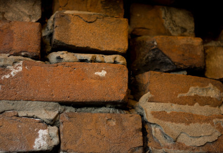 old dark brown and red brick wall with cement slurry background, old brickwork