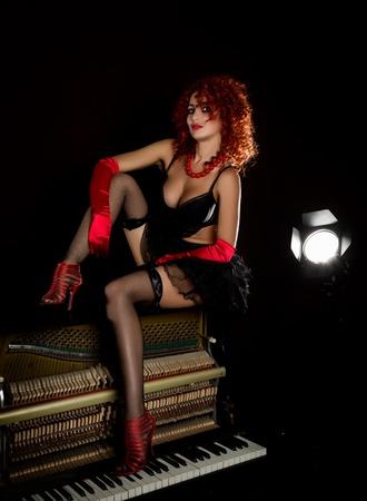 Sexy meisje ziet eruit als een pop met krullende roodharige zit op een piano, op een grijze achtergrond. Mode stijl Stockfoto