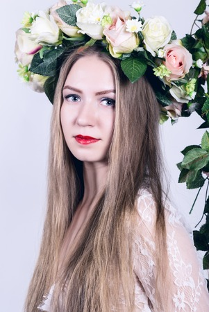 Spring beauty girl with colorful flowers wreath. Beautiful lady with blooming flowers on her head.
