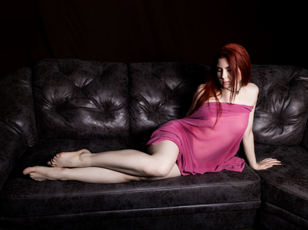 redhead beautiful sexy young woman lying on a black leather sofa on a black background