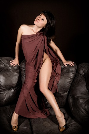 undergarments: glamour woman in a brown cape sitting on a backrest of leather sofa on a dark background