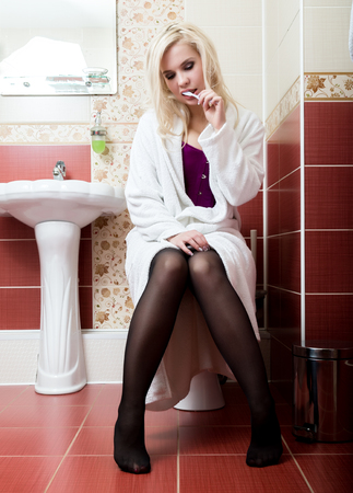 Young woman cleaning her teeth sitting on the toilet in a bathroom