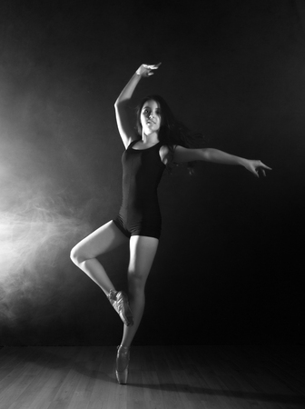 young beautiful ballet dancer in pointe shoes, dancing in a smoke on a dark background. black and white