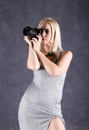 Young blonde woman in grey dress holding camera. Photographer making pictures.