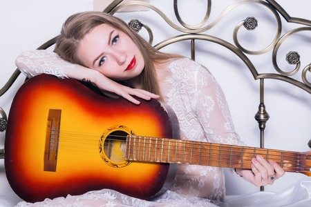 strikingly: beautiful young woman playing music on a bed with happiness and guitar Stock Photo